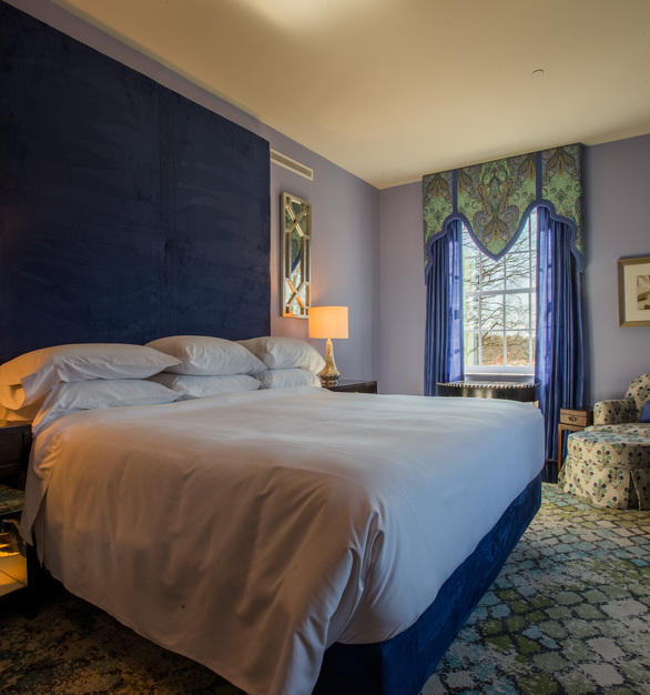 Stretch out on this comfy bed with a large upholstered headboard to relax and sleep well.