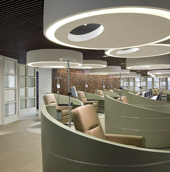 Patients at the Oncology Clinic and Infusion Suite spend as much as eight hours at a time at the infusion stations. Thus, it is important to create, as much as possible, an environment that fosters comfort and calm. Conceived as pods, the space for each infusion station is defined in two ways: 1) curved and sloped half-walls that offer patients a measure of privacy while allowing supervision from the nurses' station and 2) cylindrical soffits – distinguished from the dark, slatted-wood ceiling through the use of white gypsum board – that house multiple types of ambient and spotlighting suitable for rest or reading.