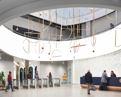 The custom sky light lets in ample amounts of natural light at 600 West Chicago--illuminating the hanging sculptures, upper circular walk way and the textured wall behind the reception desk.