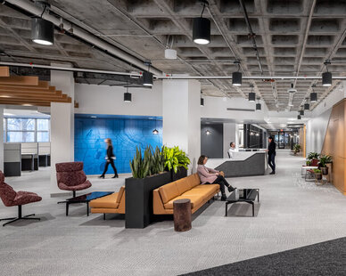 The reception area and waiting space at SRF Consulting features a unique ceiling, bright hanging lights, indoor plants and comfortable lounge furniture.   The blue graphic wall adds color to the space, while the wood ceiling beams and wood wall details add warmth to the space.