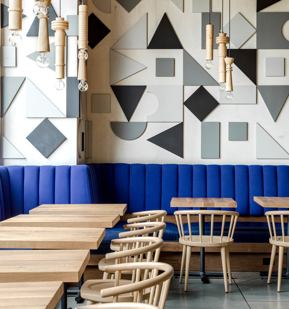 Monotone 3D monotone wall pattern juxtaposed with bright blue banquette back and natural wood table tops with dining chairs and pendants above.