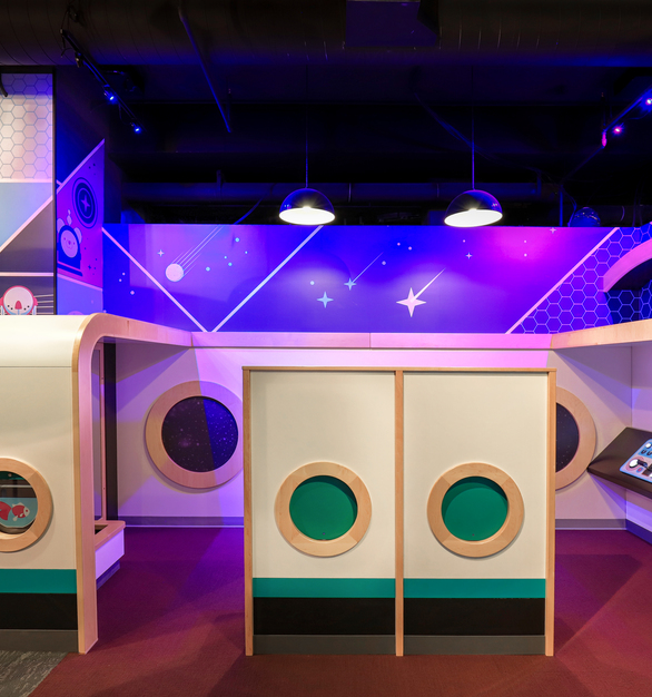 Interact with this fun space exhibit in this fun museum.  Don't forget to admire the bright wall graphics and custom lighting.