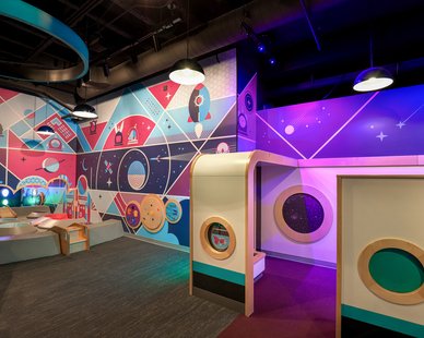 Space exploring made fun and safe in this children's play area.  Complete with custom hanging lights, wall graphics and interactive stations.