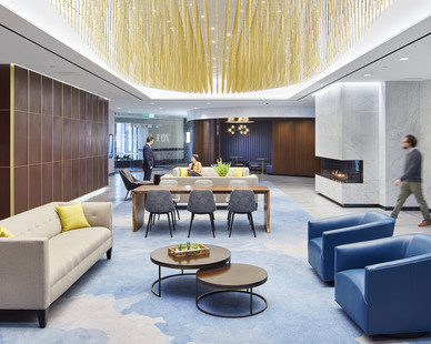 A gorgeous light installation covers the ceiling of the executive lobby and paints the room with soft light. The interior spaces include subtle beige and cream colors that are injected with lines of gold, copper and blue.