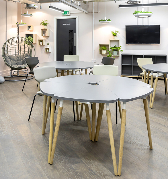 A comfortable office break room featuring the Tauko Table for aesthetically pleasing interior design.