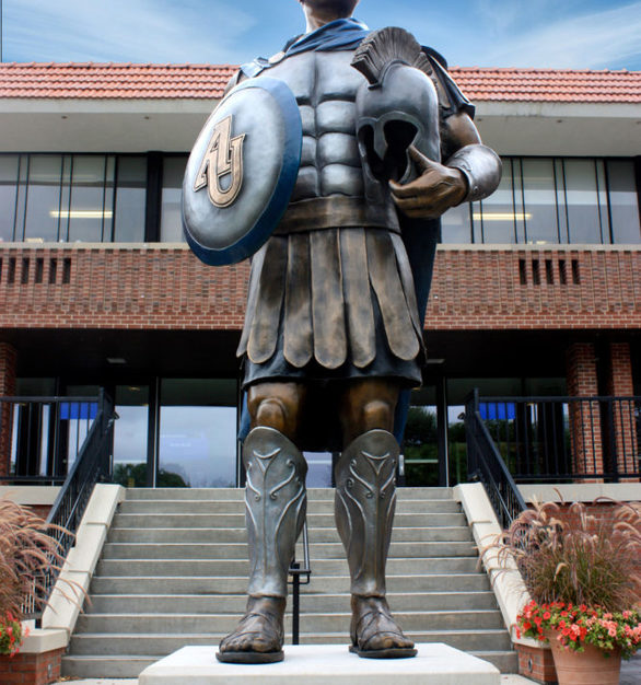"""Overlooking the courtyard of Aurora University, the bronze """"Spartan"""" mascot greets the visitors as they enter the campus."""