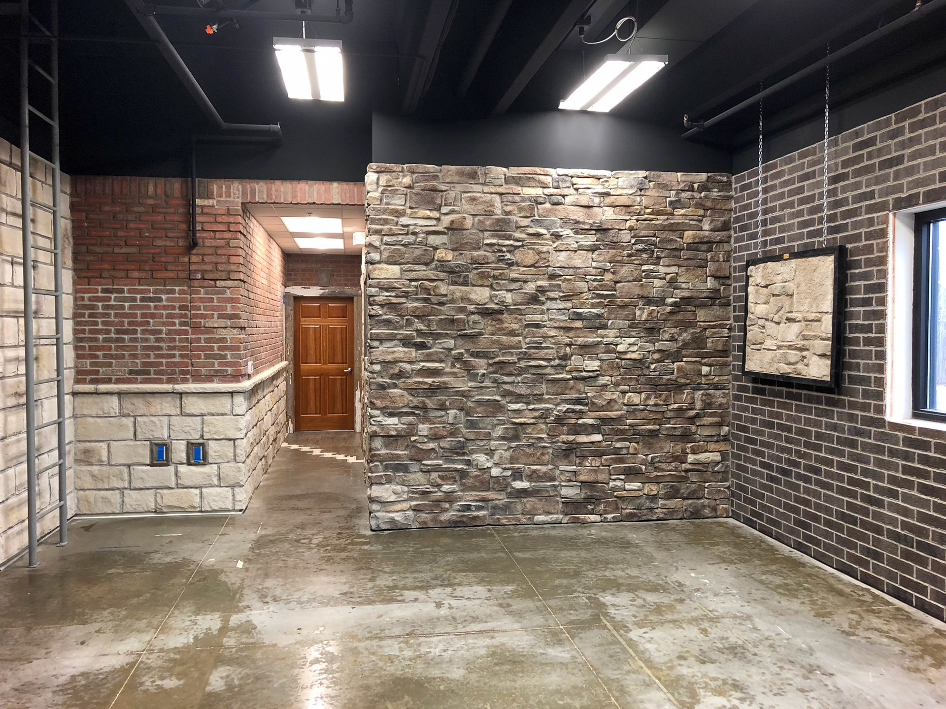 An unfurnished open office space lounge area that features stone mounted on the Speedymason Stone Lath barrier system metal lath.