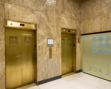The elevator space at Custom Hyatt Place features a stone wall and floor finishes and creates an elegant interior design guest can enjoy.