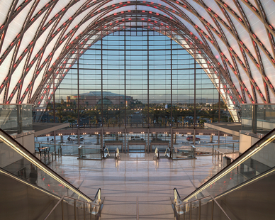 The interior at Artic Station has a large stairway and escalators for visitors. The Curved glass ceiling and large glass wall at the entrance provides ample natural light.