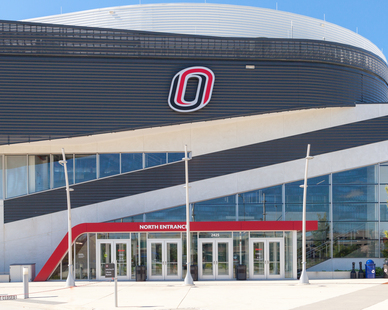 The North Entrance to Baxter Arena illuminated by lighting fixtures mounted on our Flight Pole. They are a two-piece cast aluminum with a modern base cover.