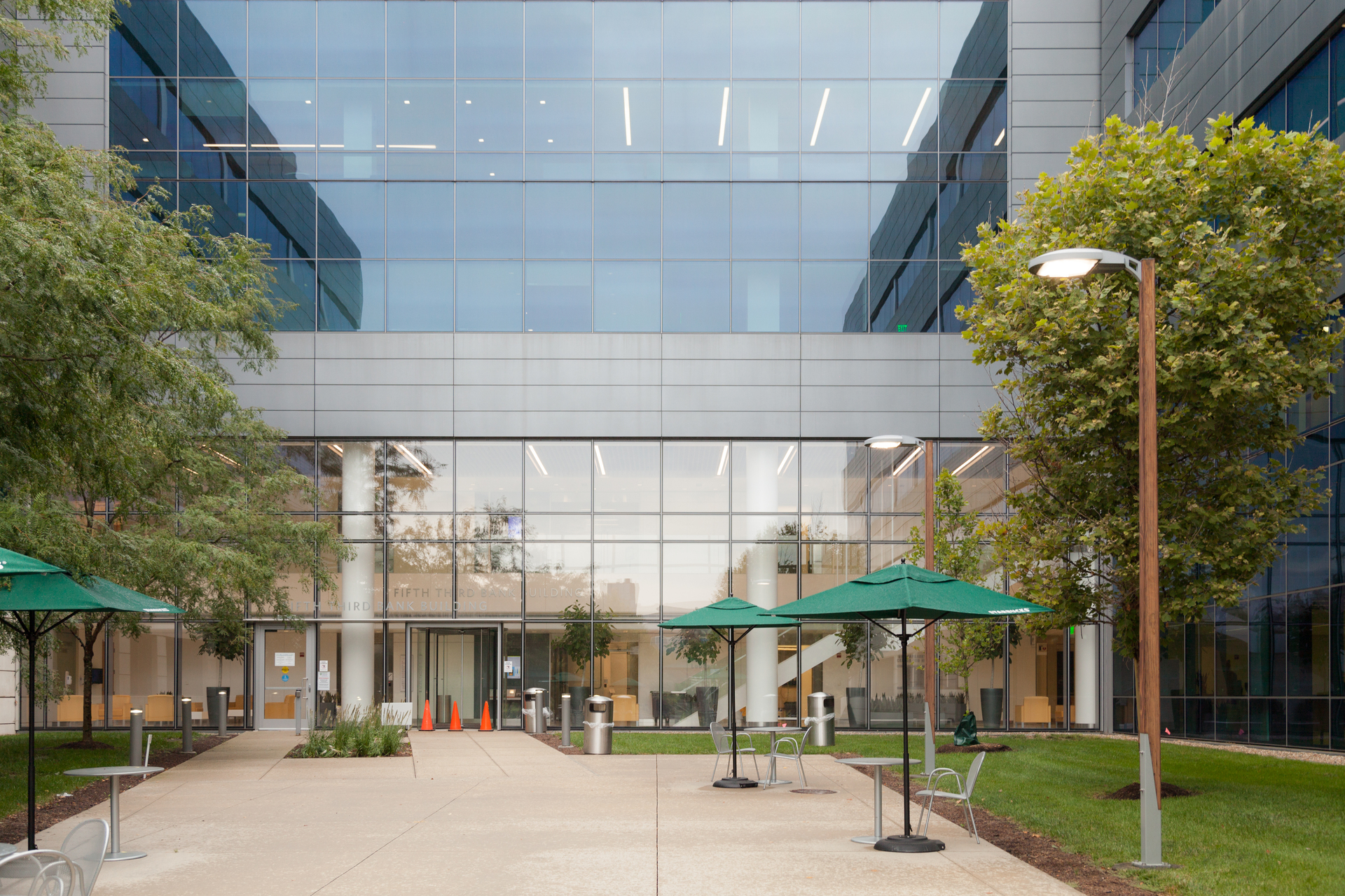 The glass facade showcases the interior lighting of the modern building design. Our Sine Pole complements the overall look for the outdoor public seating spaces.