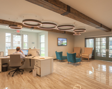 The open-concept reception and guest common area feature our Aura Ring suspended luminaire. These luminaires have a solid wood exterior and complement the wood accents throughout the space.