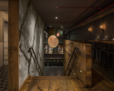 The bar's name is alluded to in the materiality and design, but in a modern way, like the riveted aged zinc wall panels.