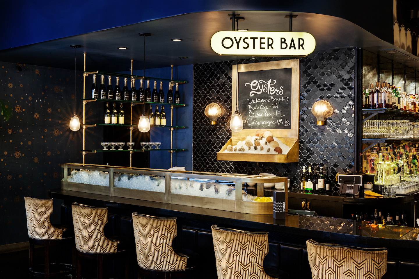 The Oyster Bar features custom brushed brass cold display cases, vintage clam-shell lighting sconces and Moroccan fish-scales mosaic tile.