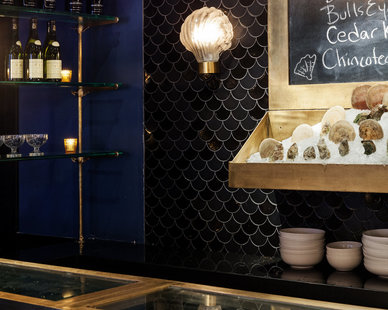 The moroccan fish-scales mosaic tiles on the wall adds a fun look to the Roxy Oyster Bar in New York, NY.
