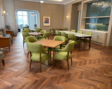 The hardwood floor in a herringbone pattern in the dining room of this senior living facility.