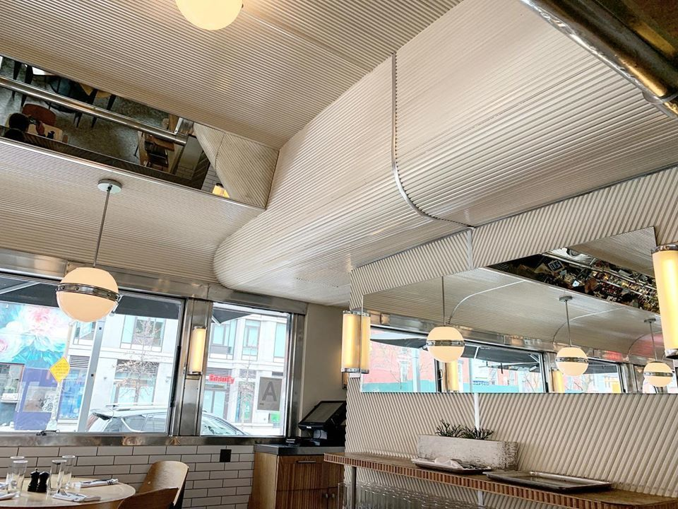 Empire Diner used flexible wall panels for the ceiling and tambour wall panels for the wall to maintain the traditional New York decor with a contemporary feel, by Surfacing Solution.