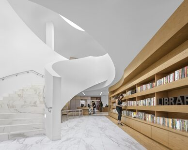 Stunning built-in white-oak shelving and marbled raised access floors flow throughout the Donald Dungan Library in Costa Mesa, California.