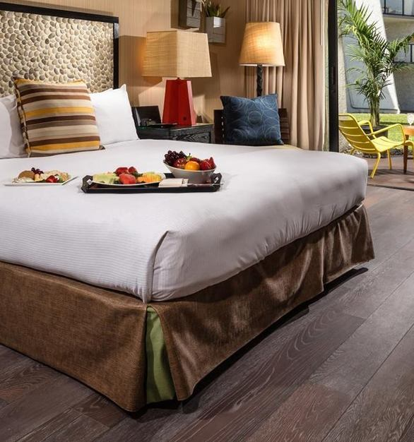 Inviting hotel suite at Hotel Maya featuring hardwood flooring by The Garrison Collection.