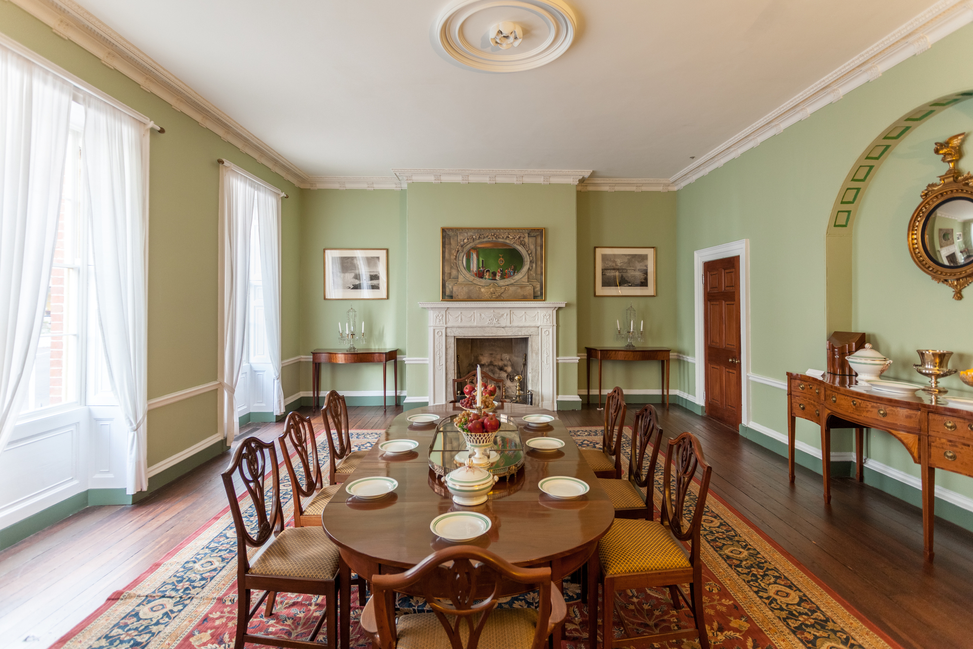 """Special furniture forms played a role in the taking of meals as well; sideboards served as staging areas for the meal.  Balance, an important classical patterning device, was achieved by placing a knife box at either end with decanters, presentation pieces, and serving plates arranged in between.  Silver plateaus served as the focal point of the dining table with dishes arranged symmetrically around the centerpiece.  One of the Tayloe granddaughters recalled, """"Lights of wax candles and pyramids of fruit, candies, grapes, and oranges at each end, which reflected in the glass, looked particularly pretty."""""""