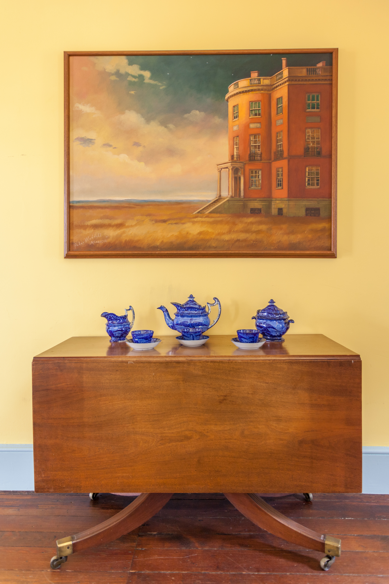 This painting was created by artist-in-residence Peter Waddell in the late-90s. It is a stylized interpretation of the land surrounding the Octagon at its construction. In 1800 the city of Washington was relatively rural yet, and the Octagon was one of the only private houses in the area.