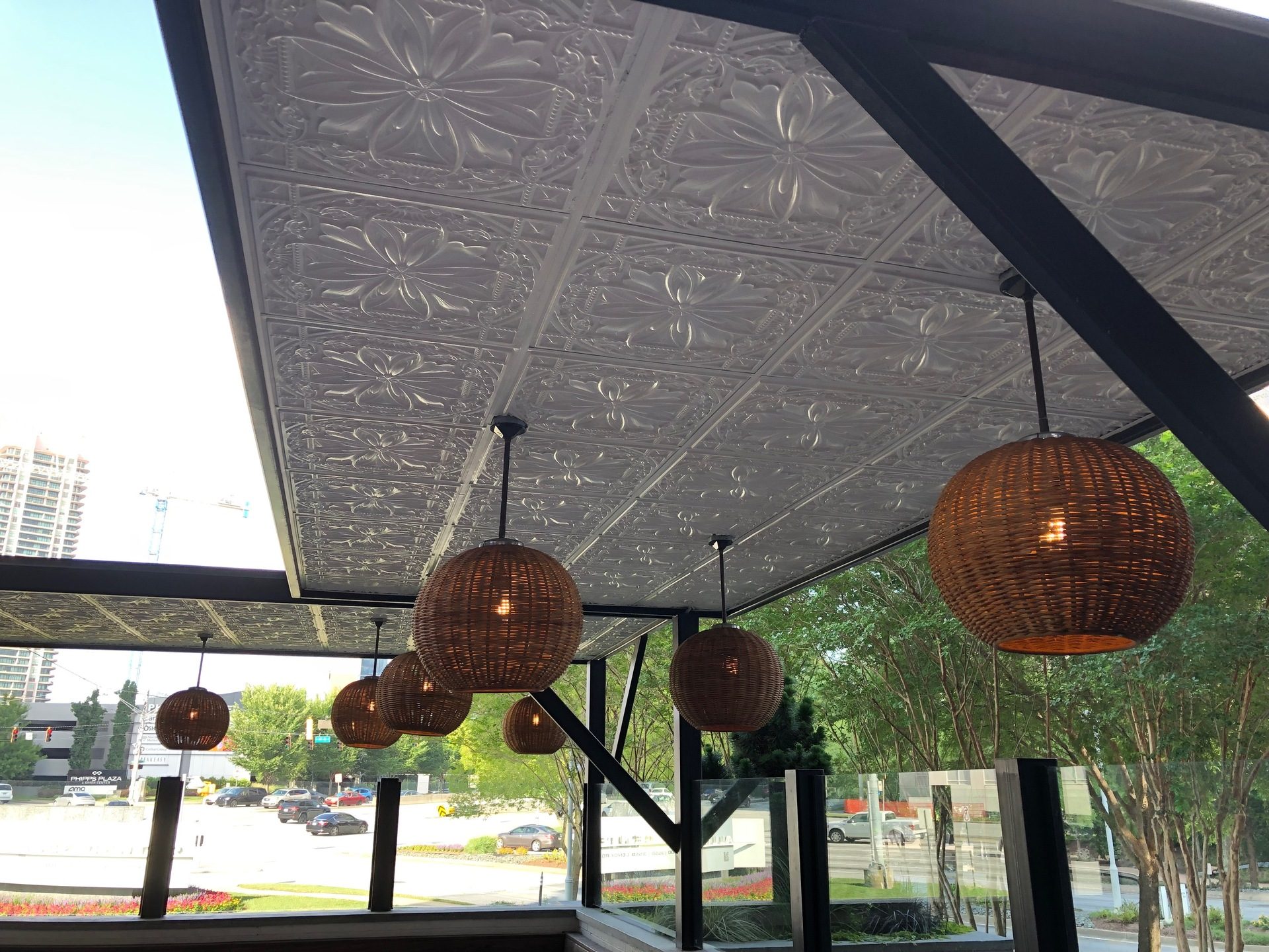 White Mediterranean-style ceiling tiles and hanging wicker lighting creates a relaxing atmosphere at this outdoor bar.