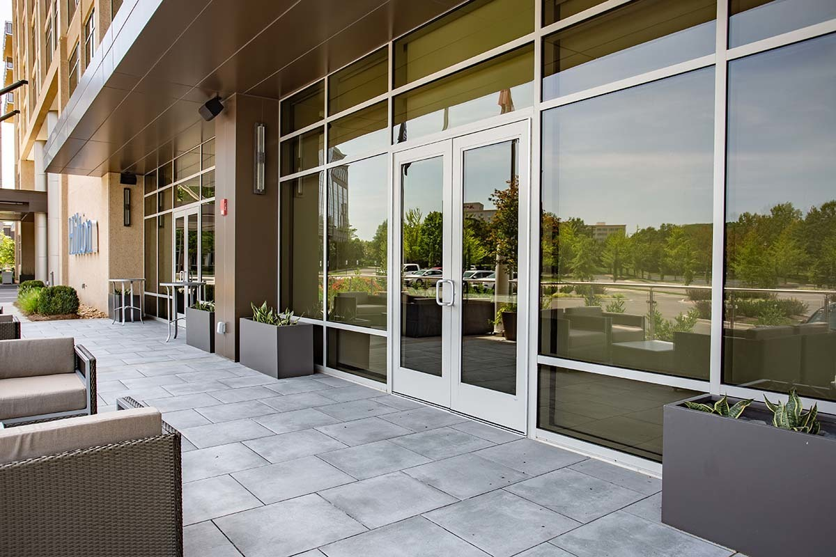 Hilton Cool Springs provides guests with a welcoming patio to enjoy. Tubelite's TerraPorte 7600 Terrace Door allows for guests easy come and go from the patio.   Photography Credit:Andi Whiskey