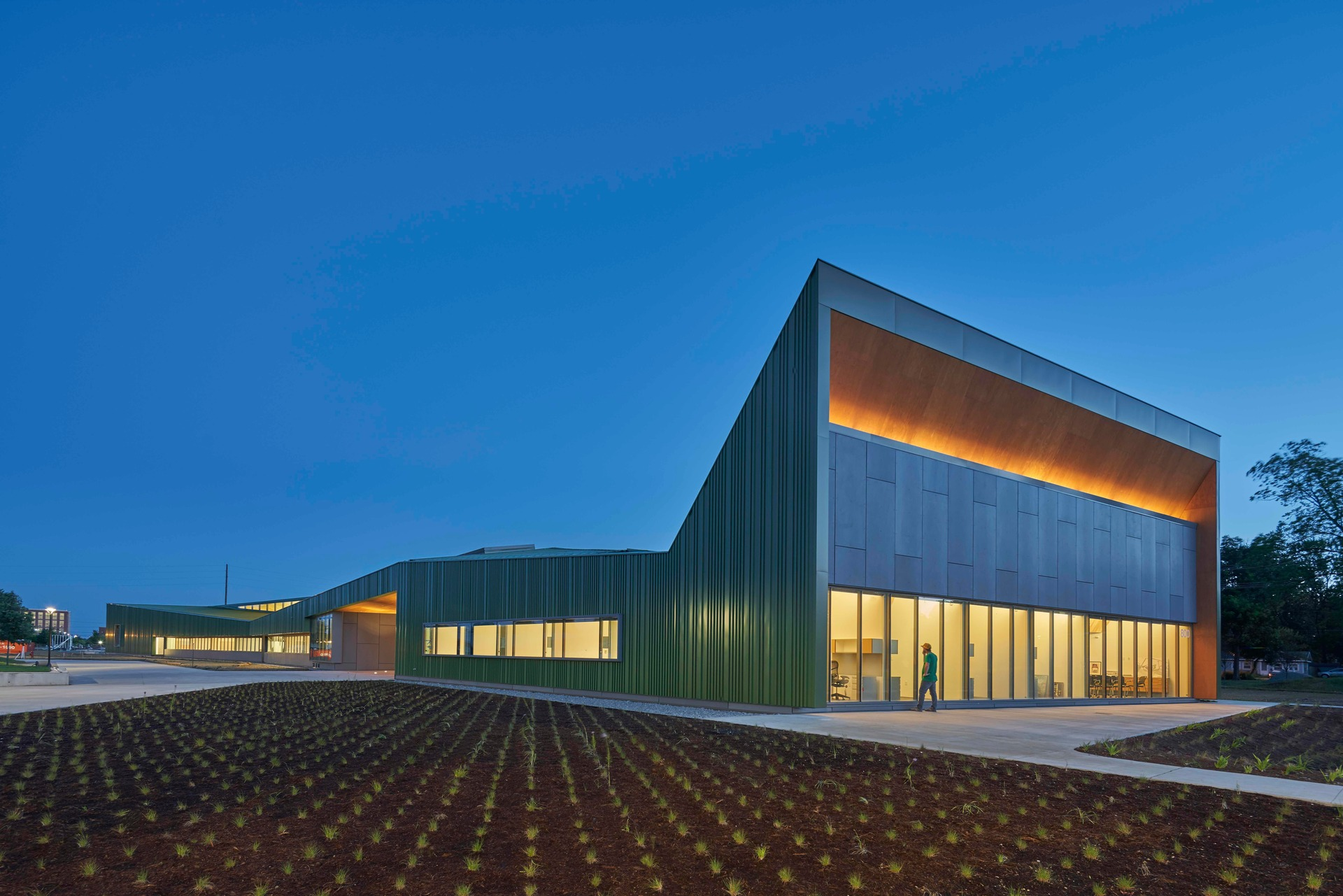 Imagining Louise Thaden viewing the school campus from the air, she would see its symmetrical elegance: The performing arts center and great hall buildings are finished in white anchoring the northeast and southwest corners, and the Reels and Wheels buildings sparkle in metallic green on the opposite corners. The structures integrate with gardens, pedestrian pathways, and an extensive trail network throughout Northwest Arkansas to connect Thaden School with its community, its culture, its ecology, its history, and its aspirations for the future.  Photo credit: Tim Hursley