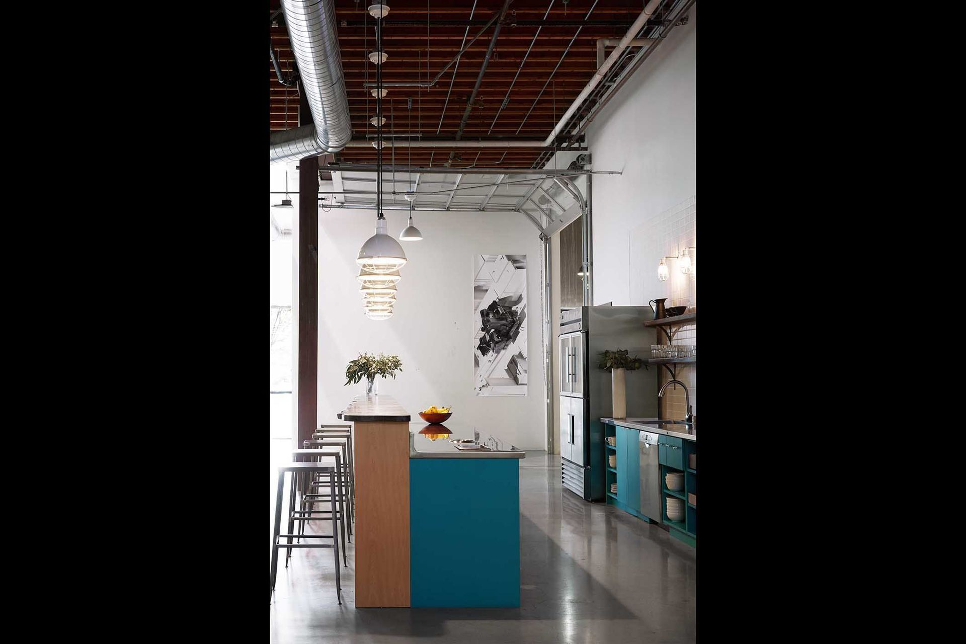 Roll-up garage doors allow various spatial configurations. Here is one of two shared kitchens within the space.