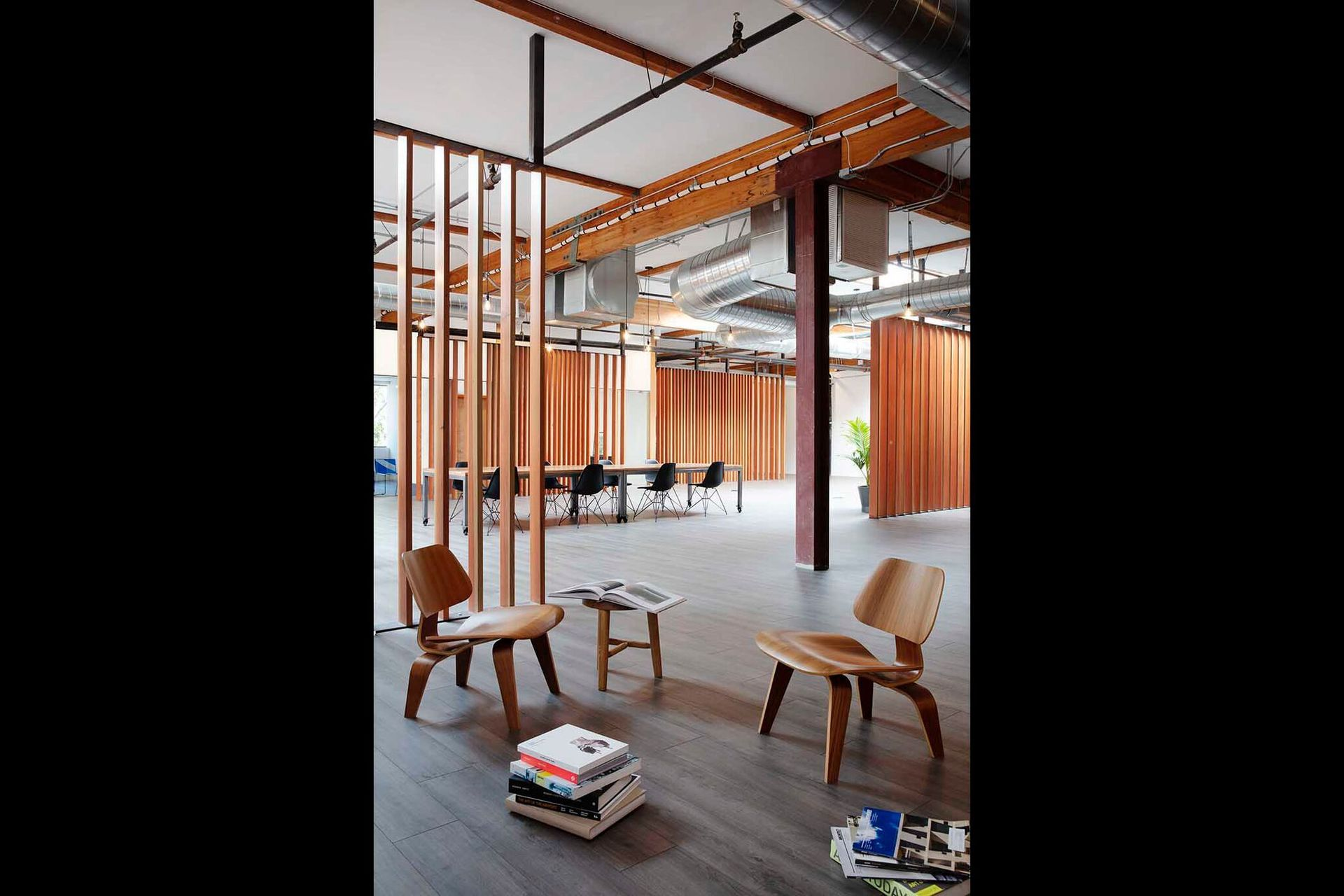 Wood slatted screens are carefully choreographed throughout to delineate space while maintaining an expansive feel. The rhythm and spacing of the slats are tuned to vary porosity and visibility according to program needs.