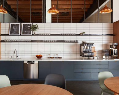 The forty-foot linear kitchen at the Psyop office becomes the creative hub and performs as the company's main all-hands meeting venue.  Photography Credit: McNulty Photo