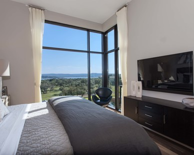 A bedroom overseeing the landscape at the Waterfall Condos on Lake Travis by Cornerstone Architects.