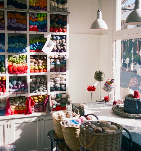 """Designer Joan Korngut states, """"We wanted illumination at the display windows but we didn't want to install a fixture that blocked the view into the store or from the store out to the street,"""" she notes. """"The scale and color of these fixtures work perfectly, and the cloth cords provide continuity with the rest of the Barn Light fixtures in the store.""""  Barn Light's Wilcox Deep Bowl Pendant Light provides light for the store, while adding to the airy, cozy environment."""