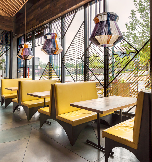 Large colorful pendants complementing bright yellow window seating.