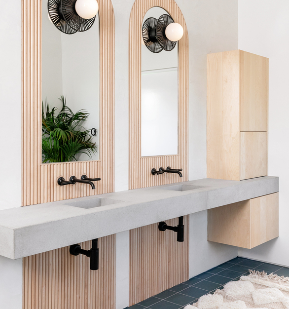 This gorgeous bathroom has solid wood tambour as an accent behind the mirrors.