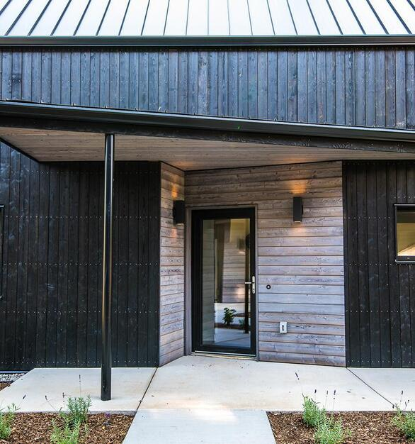 The two-toned entry of this building has black and grey siding by Pioneer Millworks.  Designed & Built by: Green Hammer Photographer: 22 Pages Photography