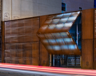 A trademark façade is created with simple awning-style warehouse doors that are clad in double layers of weathered corten steel. The panels are laser-cut with a dynamic gradient pattern and internally illuminated by concealed LED lighting to create a dramatic building facade.