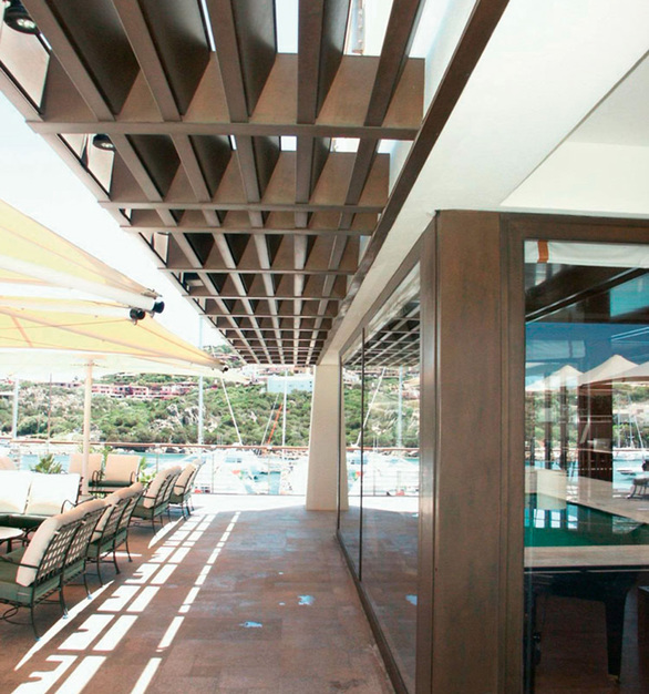 Sun screens, formed as a grating in their horizontal position, with variable geometry, are made with a steel supporting structure and covered with burnished architectural bronze alloy.